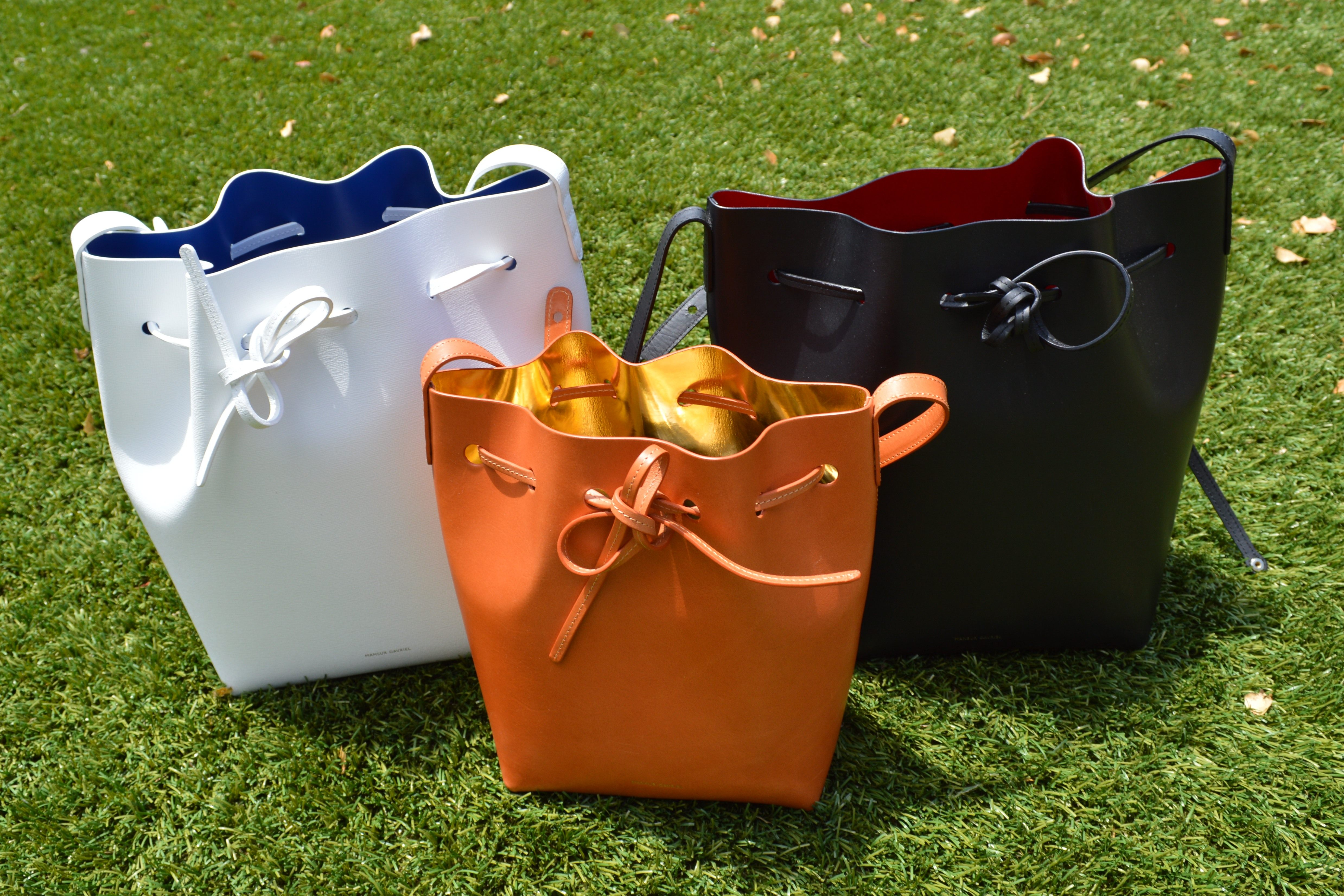 f338d5f9ac61 Pictured  Mansur Gavriel drawstring bucket bags. Black bag is vegetable  tanned leather. White bag is saffiano leather. Mini bag is vegetable tanned  leather.